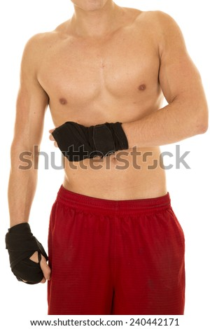 a man without a shirt on with boxing wraps on his hands. - stock photo