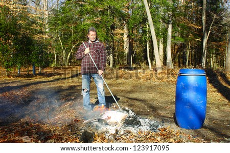 A man working a burning pile of trash and debris along side the edge of the woods - stock photo