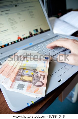 a man working at computer and making money - stock photo