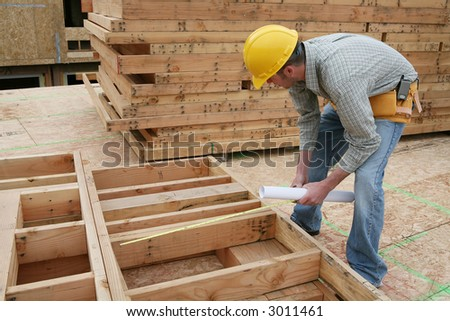 A man working building a home and measuring some wood - stock photo