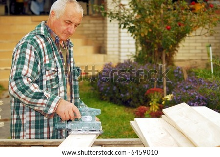 A man working building a home and sanding some wood - stock photo