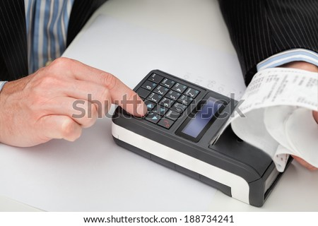 A man working on a small modern cash register with a receipt - stock photo