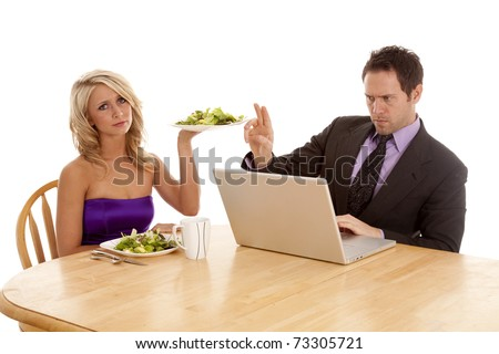 a man working on his computer the woman is trying to give him a salad to eat and he tells her with his hand to wait a minute. - stock photo