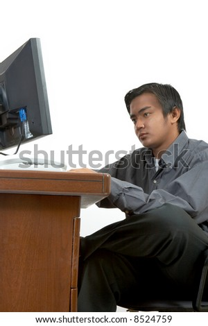 a man working on his desktop computer - stock photo