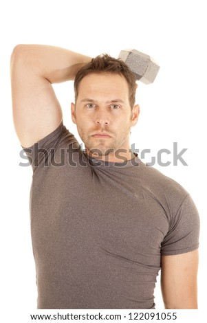 A man working out his triceps with a weight and a serious expression. - stock photo