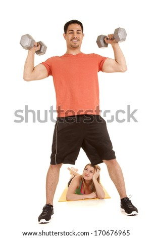A man working out with weights with a woman watching between his legs.