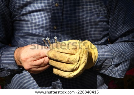 A man working outdoors holds three screws in his hands. - stock photo