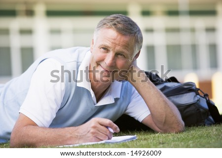 A man writing notes while lying on a campus lawn - stock photo
