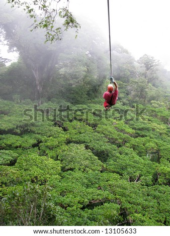 a man ziplines through the cloud forest of Monteverde, Costa Rica - stock photo
