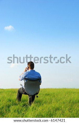 A manager sitting on a chair in nature an do a phone call with his cellphone