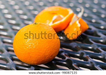 A mandarin clementine sits in front of a pile of peels - stock photo