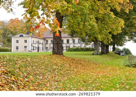 A manor, mansion and its garden, park in October.  Overcast but colorful garden with different plants of vegetation. - stock photo