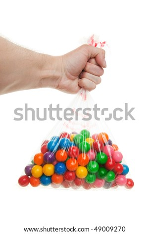 A mans arm holding out a large bag of gumballs - stock photo