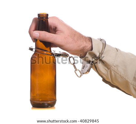A mans hand is handcuffed to a bottle of beer, isolated against a white background - stock photo