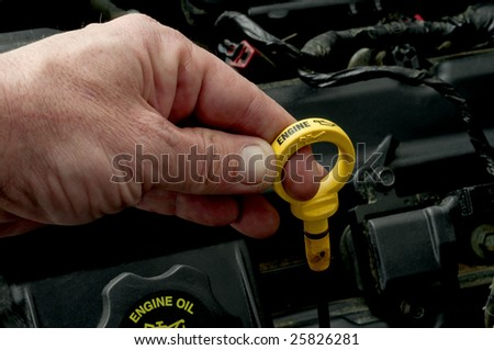 A mans hand pulling the dipstick to check the motor oil level