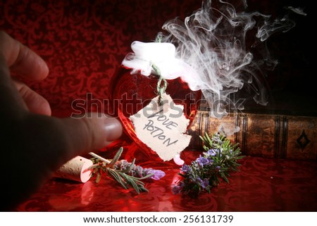 A mans hand reaches for a bottle of Freshly Brewed Love Potion, in hopes of acquiring Love. Love Potions are a Powerful substance and no to be used unwisely. Remember you might get what you ask for.  - stock photo