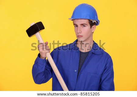 A manual worker with a sledgehammer. - stock photo