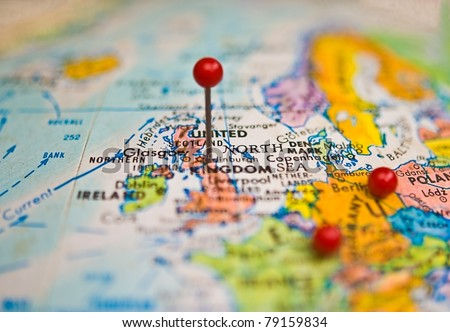 A map of the United Kingdom and surrounding areas with pins to mark places of travel. - stock photo