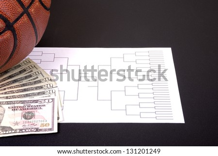 A March Madness tournament bracket with a basketball and fanned money - stock photo