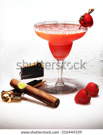 a Margarita strawberry cocktail with a cigar,strawberries,a lighter and ? cut cigar machine with drops on background - stock photo
