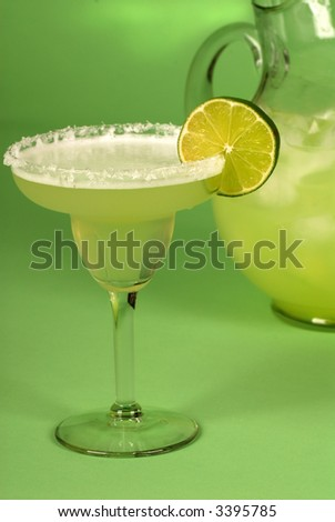 A margarita with a pitcher of margaritas behind it