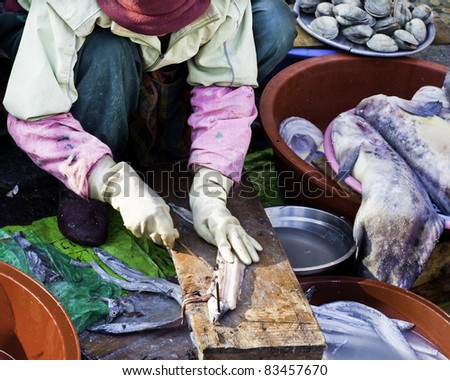 A market lady is cleaning the fish in the Chinese market - stock photo