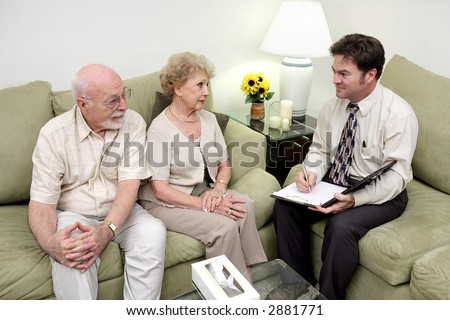 A marriage counselor or salesman meeting with a senior couple.  The wife is receptive but the husband looks skeptical - stock photo