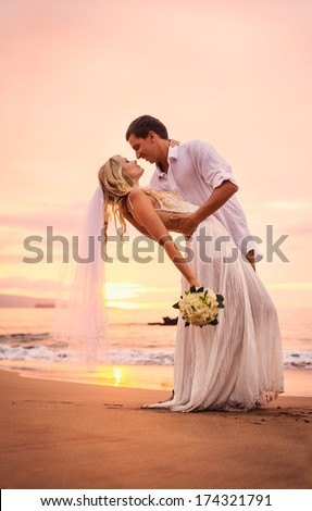 A married couple, bride and groom, at sunset on a beautiful tropical beach - stock photo