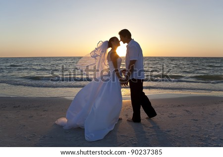 A married couple, bride and groom, kissing at sunset on a beautiful tropical beach - stock photo