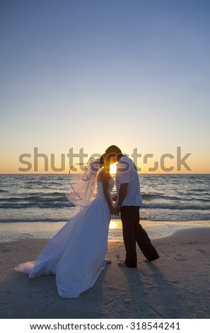 A married couple, bride and groom, kissing at sunset sunrise wedding on a beautiful tropical beach - stock photo
