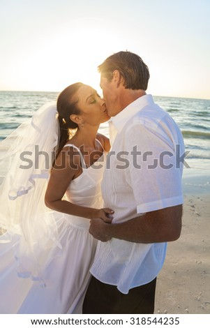 A married couple, bride and groom, kissing sunset sunrise on a beautiful tropical beach - stock photo