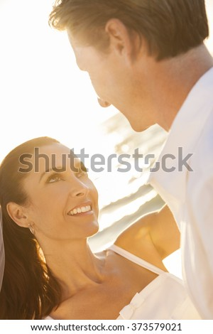 A married couple, bride and groom, together in sunset sunshine on a beautiful tropical beach - stock photo