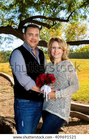 A married couple poses for a picture celebrating their anniversary.  The wife is holding a rose bouquet to remind her of her wedding flowers. - stock photo