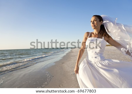 A married woman bride in her wedding dress in golden evening sunshine on a beautiful tropical beach - stock photo