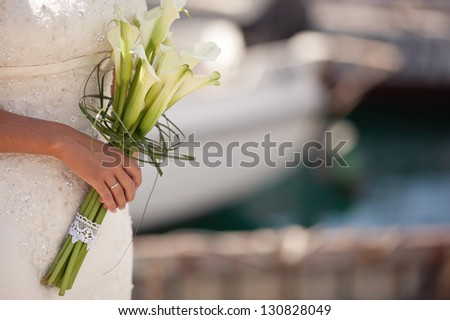 a married woman holding a bouquet of white lilies - stock photo