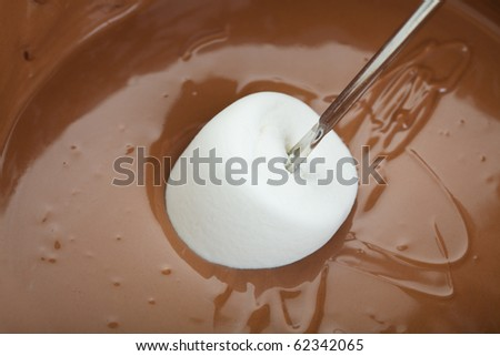 A marshmallow that has just been freshly dipped in warm milk chocolate fondue.  Shot on white background. - stock photo