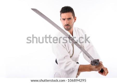 a martial arts man wielding a sword. Studio portrait - stock photo