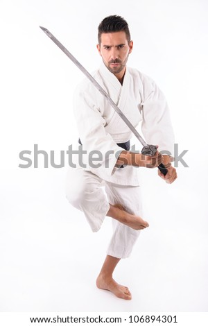 a martial arts man with a sword standing - stock photo
