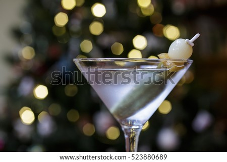 A martini alcoholic drink with garnish in front of a Christmas tree.