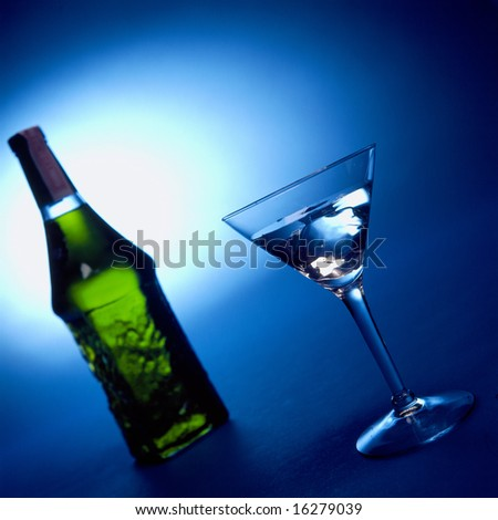 A martini glass and green bottle - stock photo
