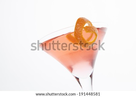 A martini glass is filled with a pink cosmopolitan cocktail with a piece of orange garnish on the rim; horizontal format, white background - stock photo