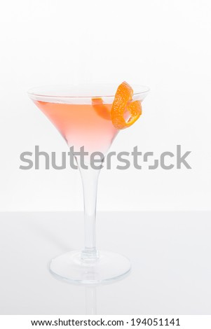 A martini glass is filled with a pink cosmopolitan cocktail with a piece of orange garnish on the rim; vertical format, white background and surface