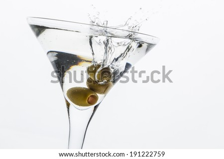 A martini glass on a white background; the water ripples and splashed as a green spanish olive with pimento is dropped into the glass; horizontal format - stock photo