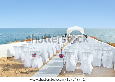 A marvelous place in the decorations and flowers for the wedding ceremony. With white chairs on the sea. - stock photo