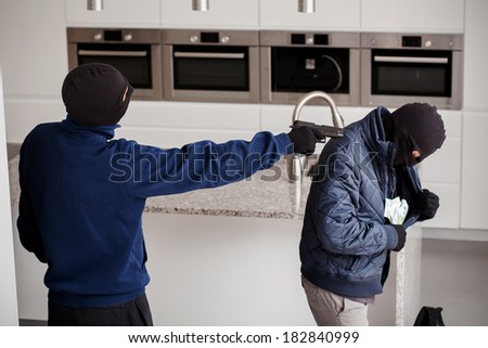 A masked burglar aiming at his accomplice - stock photo