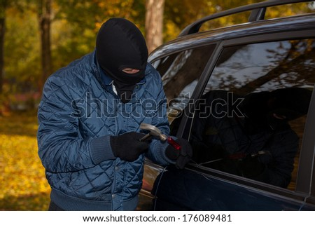 A masked criminal about to steal a car - stock photo