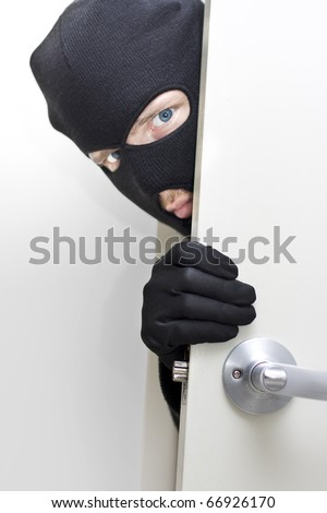 A Masked Intruder Peers Around The Corner While Breaking In A Properties Front Door - stock photo