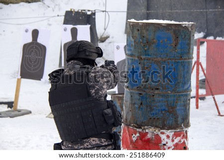 A masked man at the shooting range - stock photo