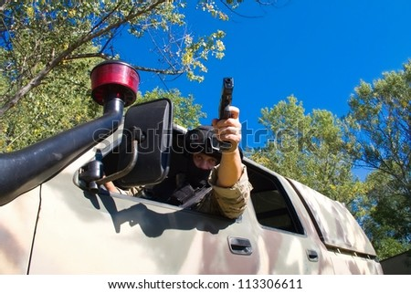 A masked man with a gun - stock photo