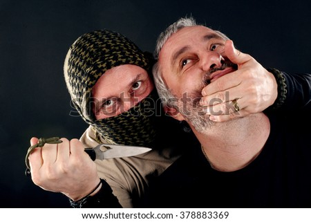 a masked man with a knife attacked another man - stock photo